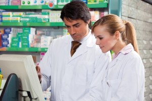 portrait of two pharmacists looking at computer monitor